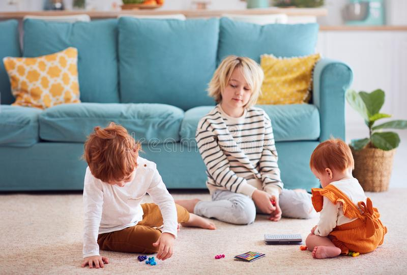 Cute kids, siblings playing on the floor at home royalty free stock image