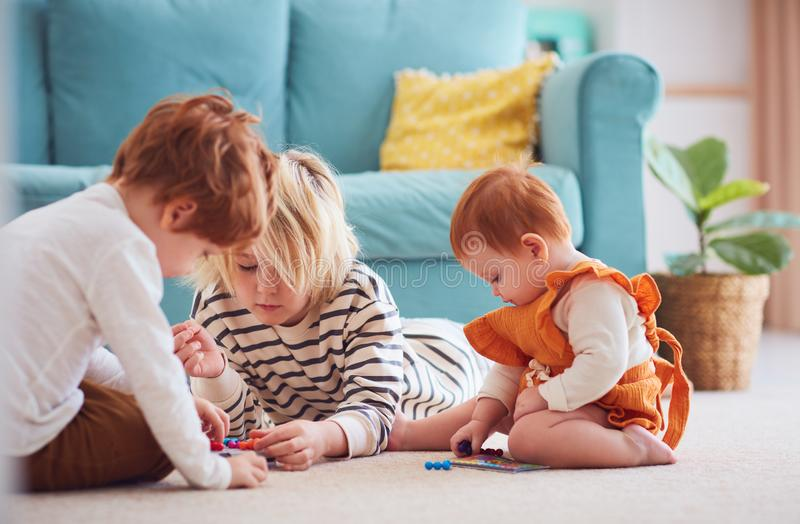 Cute kids, siblings playing together on the floor at home royalty free stock photography