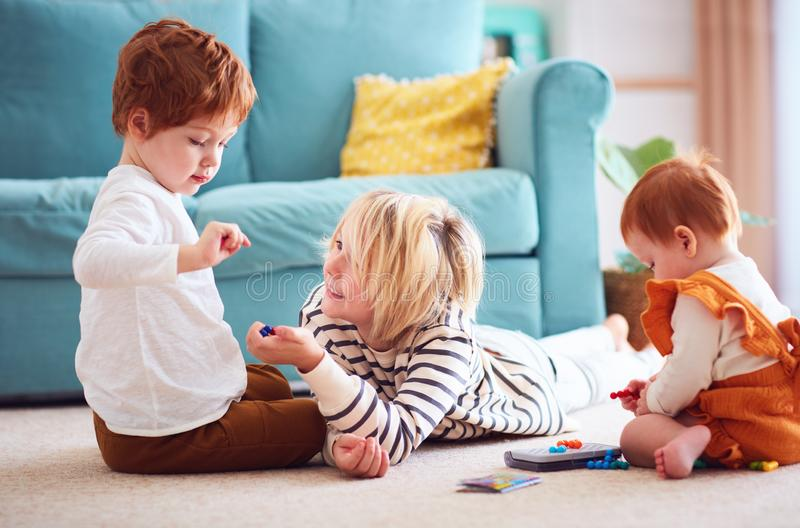 Cute kids, siblings playing together on the floor at home stock photos
