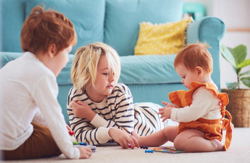 Cute kids, siblings playing together on the floor at home royalty free stock photo