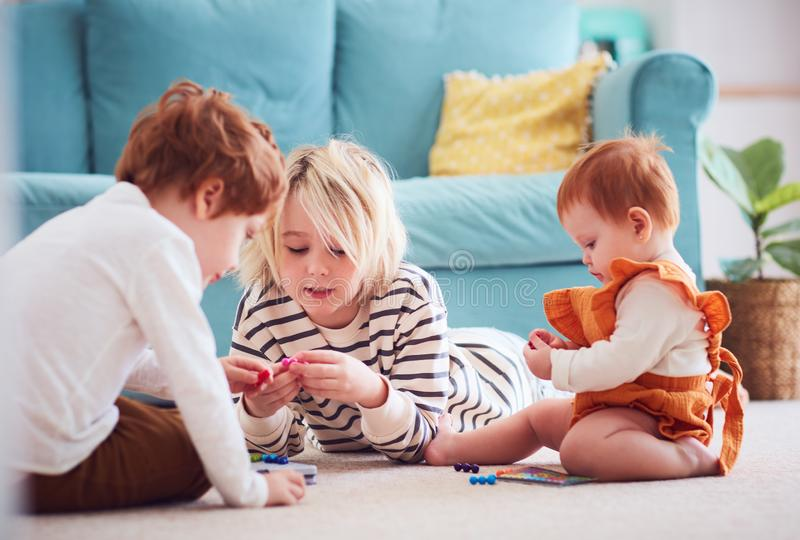 Cute kids, siblings playing together on the floor at home stock photography