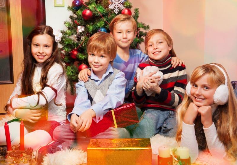Cute kids sitting near Christmas tree royalty free stock photos
