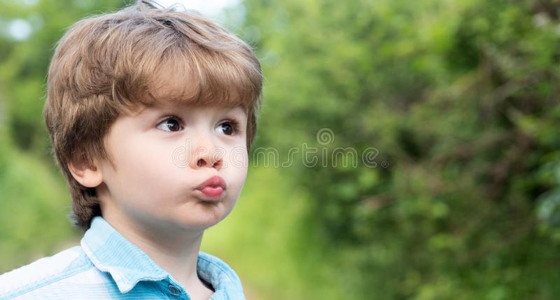 Cute kiss. Child with kiss icon gesture. The little boy made funny lips. Preschooler. Love and family. Surprised child stock photo