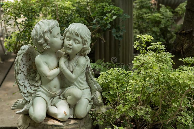 Cute kissed couple cupid in garden stock photos