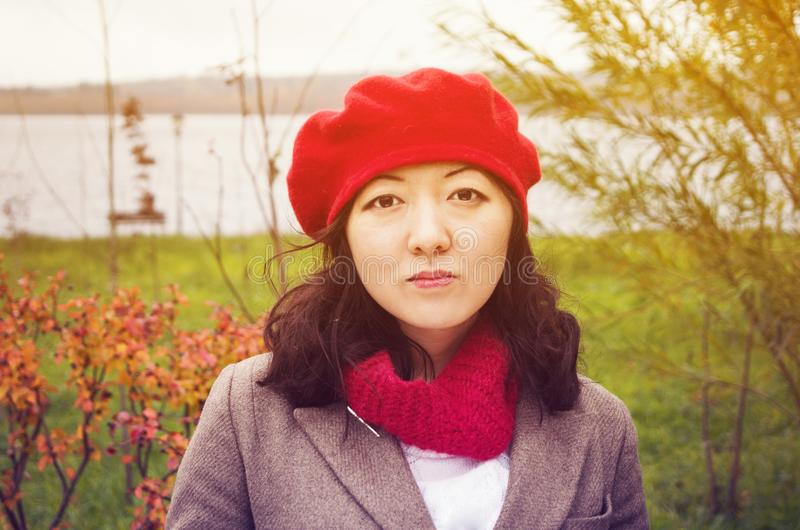 A cute Korean girl wearing beige coat and red beret hat outdoors near the lake in autumn. October mood royalty free stock photo