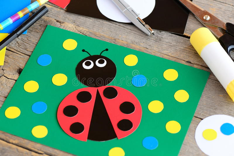 Cute ladybug cardboard card. Green card with ladybug made from cardboard, scissors, glue stick, pencil, marker, cardboard sheets. Summer crafts idea for kids stock images