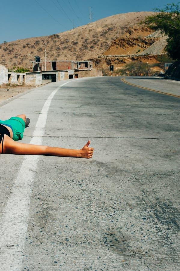 Cute American woman hitchhiking. Cute latin American woman hitchhiking royalty free stock photography