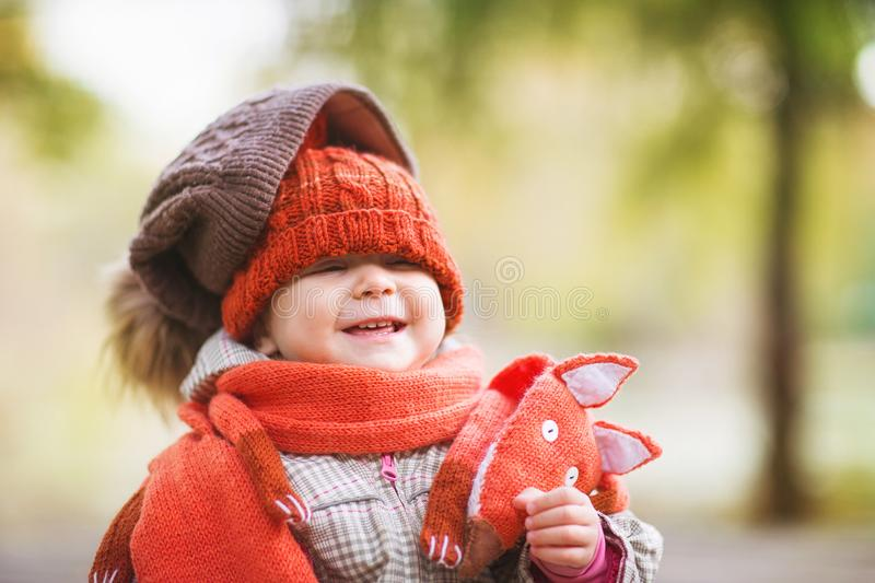 Cute laughing baby in autumn clothes. child in knitted hats and scarf. Orange animal is fox. concept: warm clothing, cold weather royalty free stock images