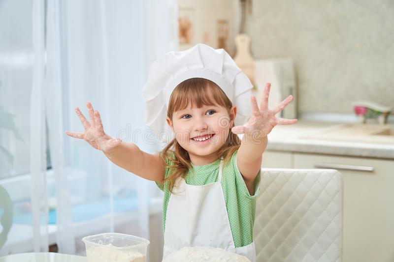 Cute laughing baby cook waving his hands, stretched out his hands and opened his palms showing happiness. Self-cooking children royalty free stock image