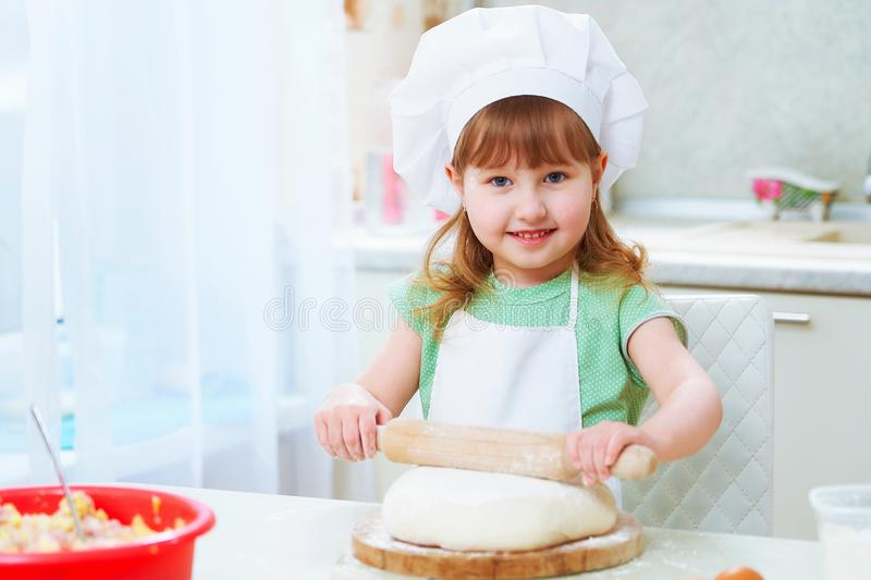 Portrait of cute baby chef happiness laughing. A cute laughing kid chef rolls out the dough with a rolling pin, a little girl looks up and smiles.a child at home stock photography