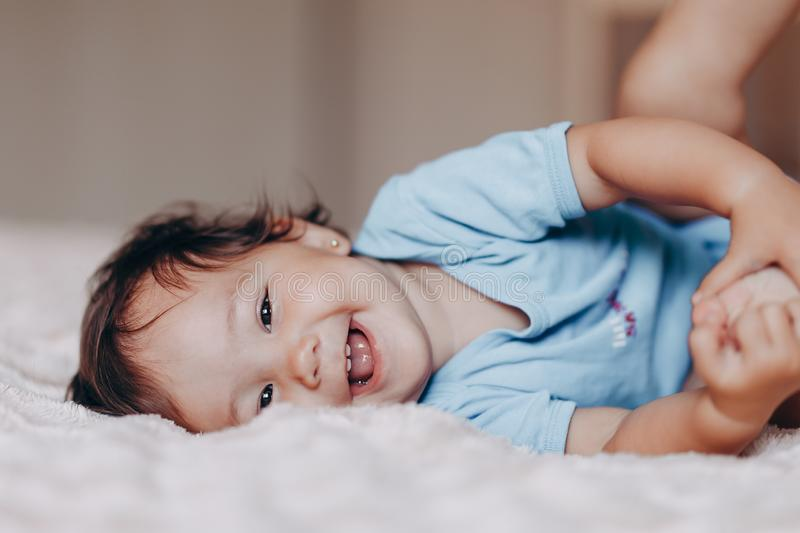 Cute laughing one year old girl lying on bed and looking at camera touch her feet.  royalty free stock photo