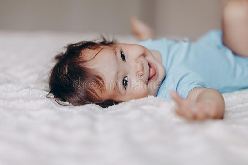 Cute laughing one year old girl lying on bed and looking at camera touch her feet.  stock photography