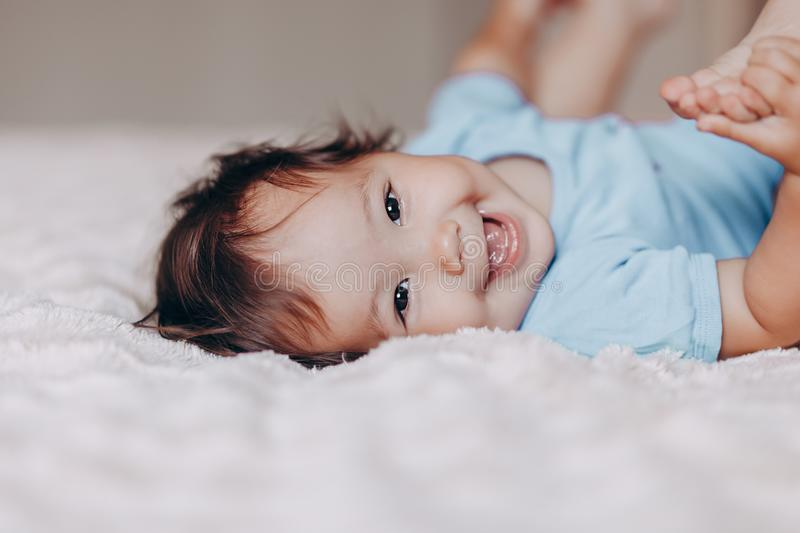 Cute laughing one year old girl lying on bed and looking at camera touch her feet.  royalty free stock photos