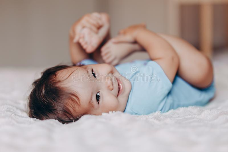 Cute laughing one year old girl lying on bed and looking at camera touch her feet.  stock images