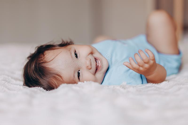 Cute laughing one year old girl lying on bed and looking at camera touch her feet.  royalty free stock photography