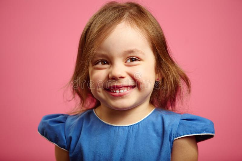 Cute laughter of female child, has confused face, shyly shrugged shoulders. stock image