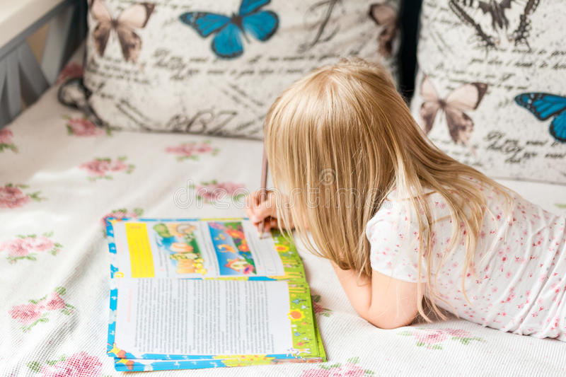Cute liitle blonde girl lying on a bed and making hometasks in the workbook with a pencil in a hand.  royalty free stock photo