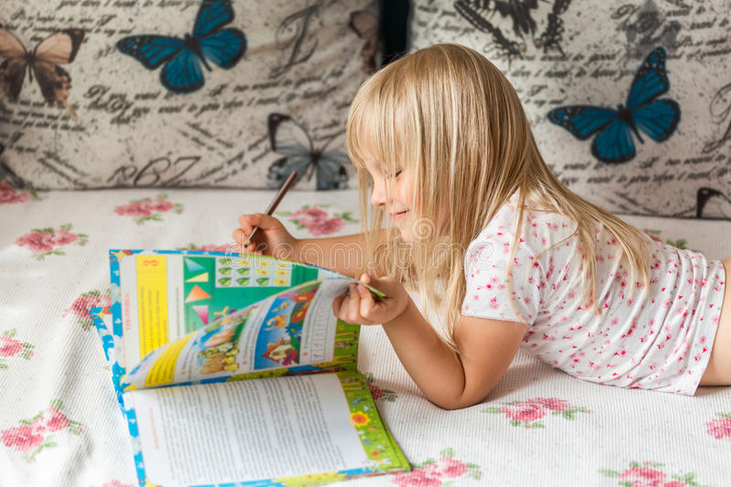 Cute liitle blonde girl lying on a bed and making hometasks in the workbook with a pencil in a hand. Smile. Back to school concept royalty free stock image