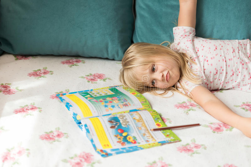 Cute liitle blonde girl lying on a bed and making homework in the workbook with a pencil. Girl is tired. End of vacation and back to school concept royalty free stock photography