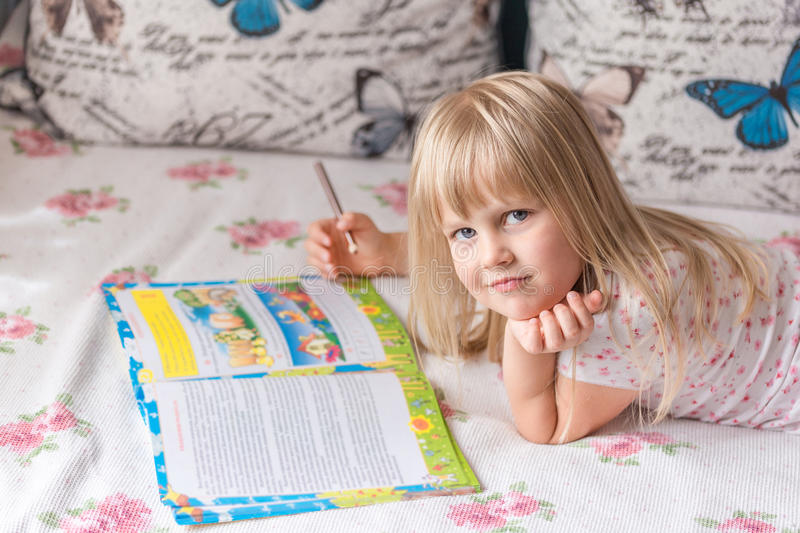 Cute liitle blonde girl lying on a bed and making homework in the workbook with a pencil. Girl is tired. End of vacation and back to school concept stock image