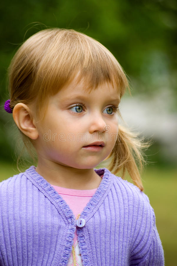 Cute liitle girl close-up. Cute liitle girl in light violet close-up royalty free stock image