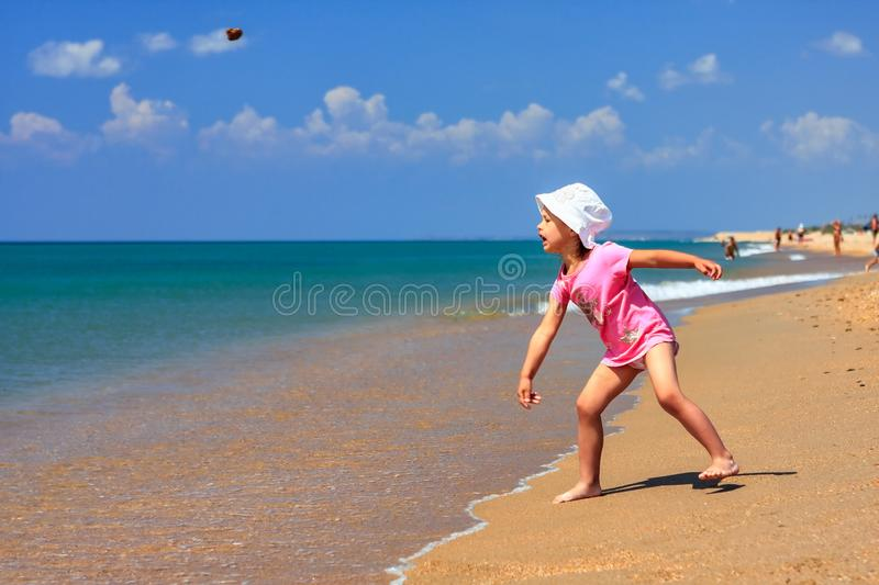 Cute little active Caucasian girl on sandy beach at summer seaside throwing stone into the sea on sunny day on blue sky background royalty free stock image