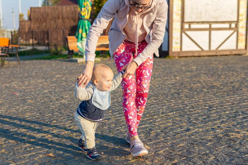Cute little adorable blond toddler boy making first steps with mother support at city park at evening sunset time. Happy funny stock image