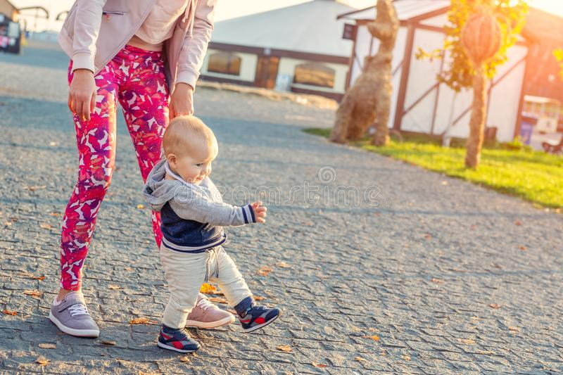 Cute little adorable blond toddler boy making first steps with mother support at city park at evening sunset time. Happy funny stock images