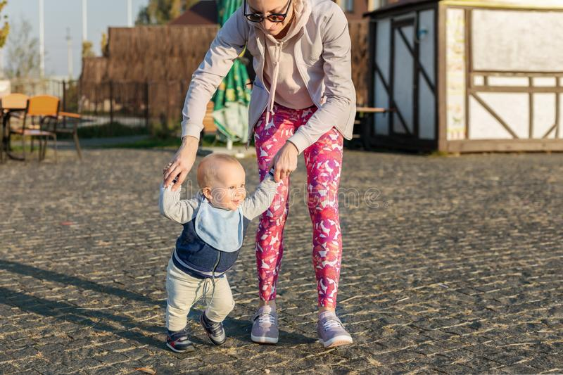 Cute little adorable blond toddler boy making first steps with mother support at city park at evening sunset time. Happy funny stock photos