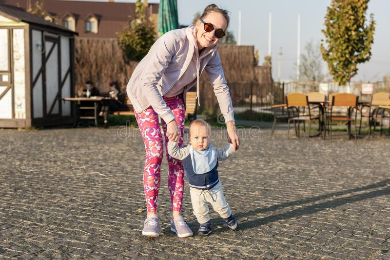 Cute little adorable blond toddler boy making first steps with mother support at city park at evening sunset time. Happy funny royalty free stock photography