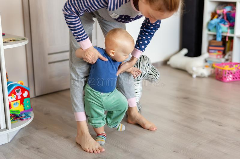 Cute little adorable blond toddler boy making first steps with mother support in playroom at home. Happy funny child royalty free stock photo