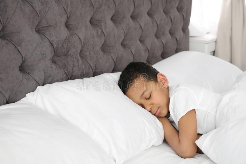 Cute little African-American boy sleeping in bed. stock photo