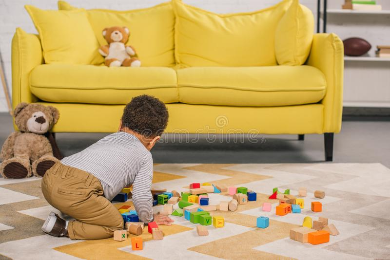 Cute little african american child playing with colorful blocks on carpet. At home royalty free stock photography