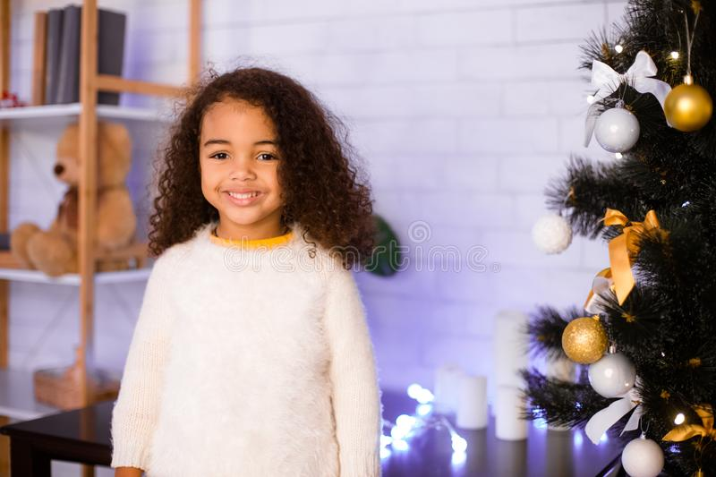 Cute little african american girl near decorated Xmas tree royalty free stock photos