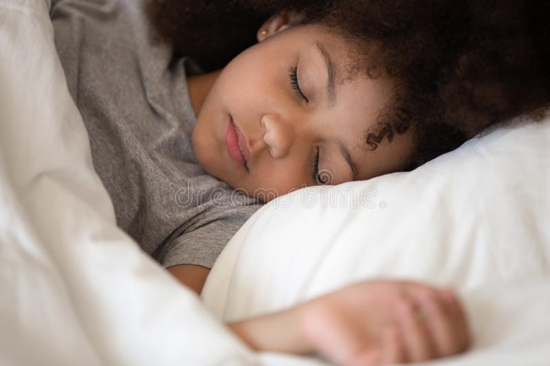 Cute little african american kid girl sleeping alone in bed stock photo