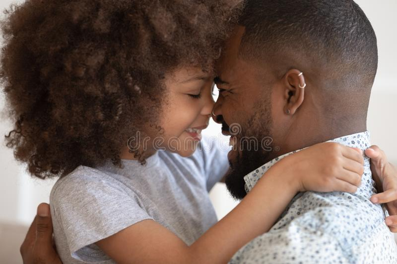 Cute little african daughter embrace touch noses with happy dad royalty free stock photo