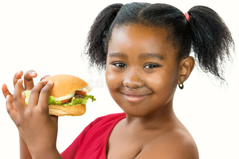 Cute little african girl holding appetizing hamburger. stock photo