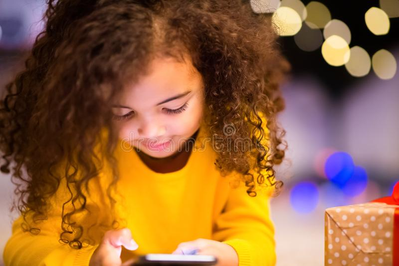 Cute little african girl playing with cell phone at Christmas eve stock photos