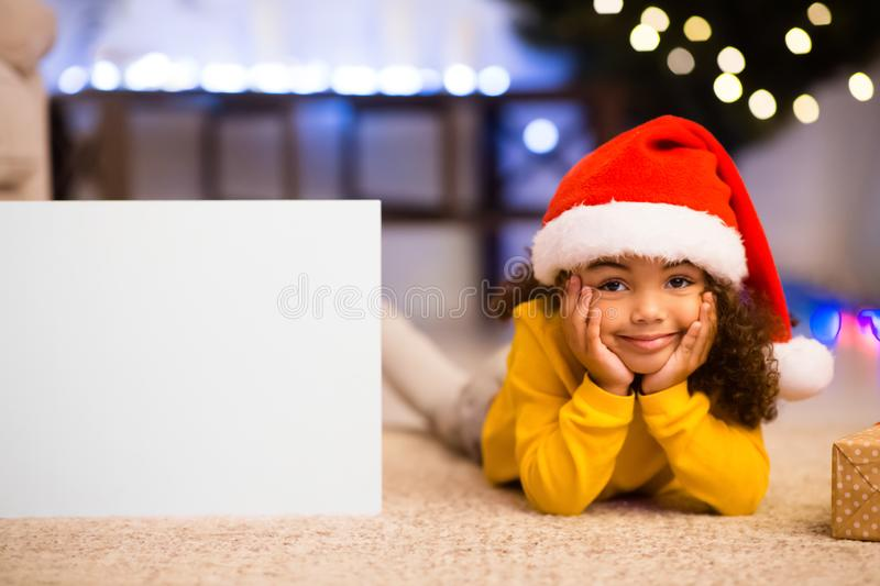 Cute little african girl in Santa hat lying next to blank poster stock photos