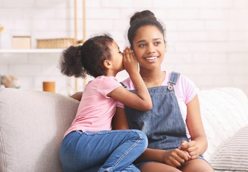 Cute little african girl whispering something to her elder sister ear stock photo