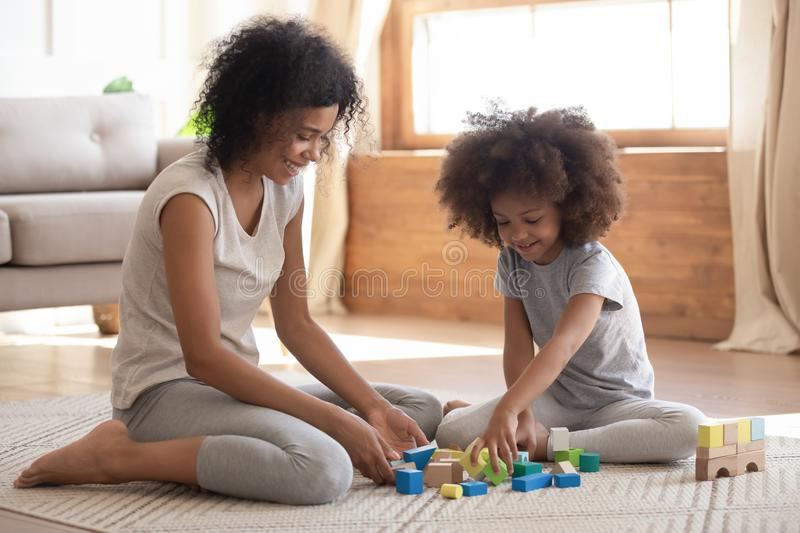 Cute little african kid playing with black mom on floor. Cute little african american kid playing with black mom or baby sitter on floor, happy family mixed race royalty free stock images