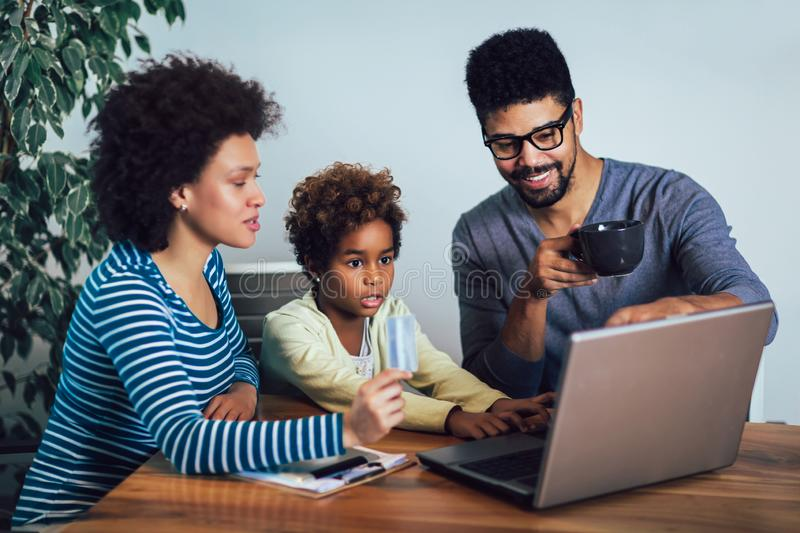 Little Afro-American girl and her beautiful young parents using a laptop and doing shopping online. Cute little Afro-American girl and her beautiful young stock images