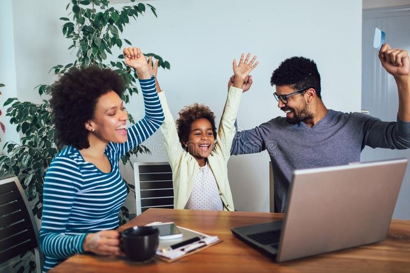 Little Afro-American girl and her beautiful young parents using a laptop and doing shopping online. Cute little Afro-American girl and her beautiful young stock photography