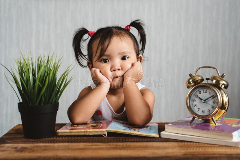 Cute little asian baby toddler making boring face while reading books with alarm clock. Child growth, early education and learning concept stock images