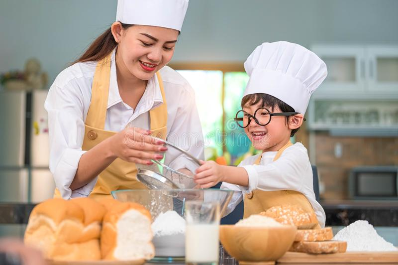 Cute little Asian boy and beautiful mother sifting dough flour with sifter sieve colander in home kitchen on table for prepare to royalty free stock photography
