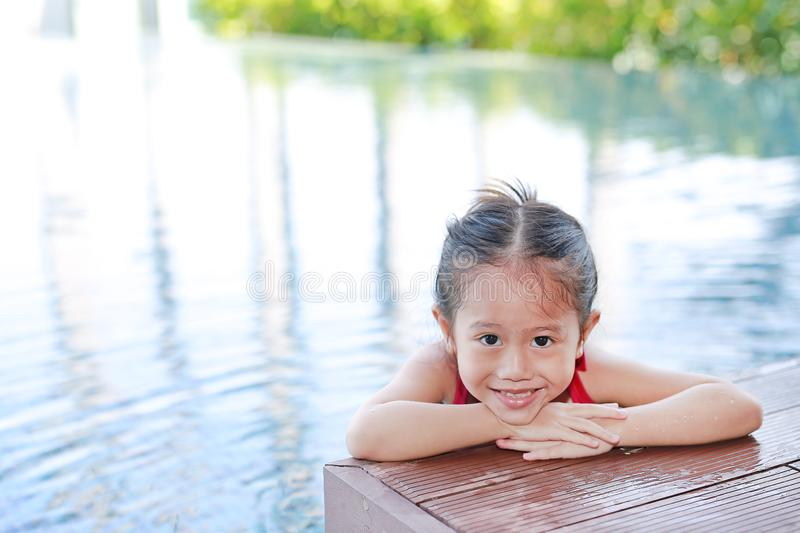 Cute little Asian child girl in a mermaid suit has fun sitting poolside.  royalty free stock photos