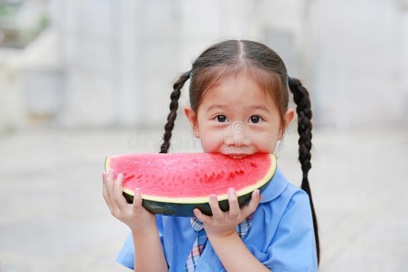 Cute little Asian child girl in school uniform enjoy eating fresh sliced watermelon.  royalty free stock photography