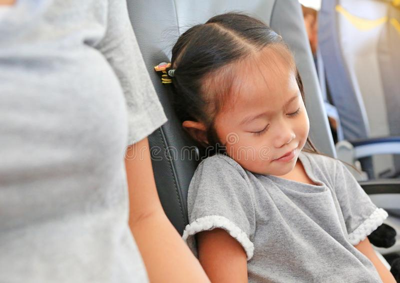 Cute little Asian child girl sleeping on the seat of airplane beside her mother stock images