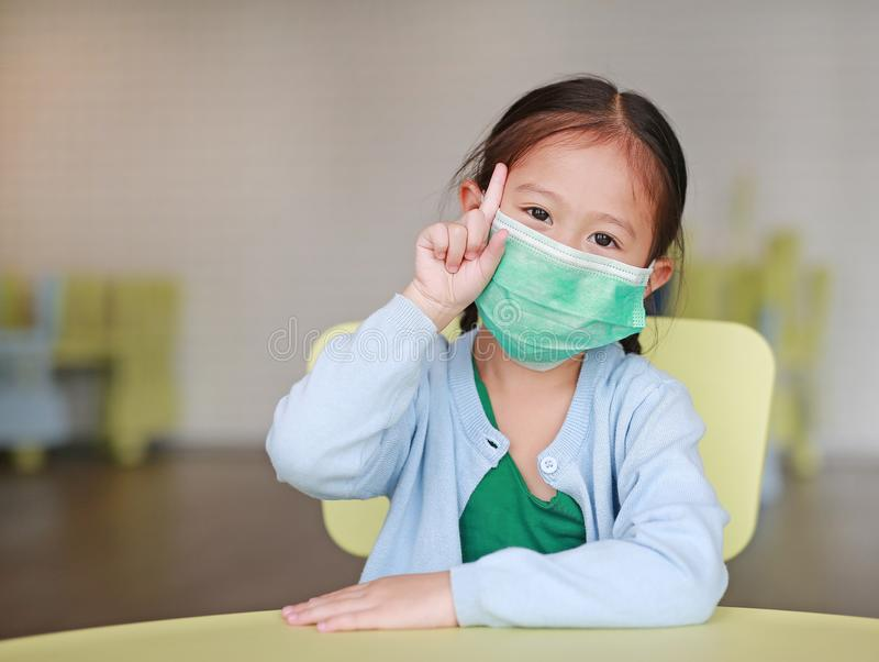 Cute little Asian child girl wearing a protective mask with showing one forefinger sitting on kid chair in children room.  stock image