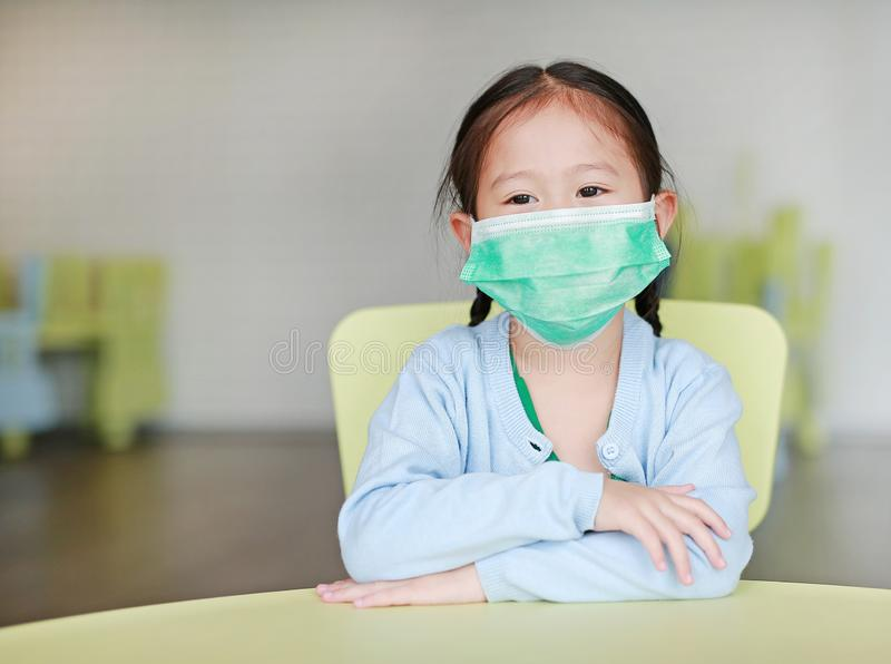 Cute little Asian child girl wearing a protective mask sitting on kid chair in children room royalty free stock photos